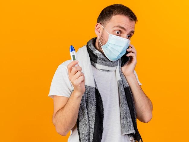 Patrząc na bok, zaskoczony młody chory w czapce zimowej i masce medycznej mówi przez telefon i trzyma termometr na białym tle na żółtym tle