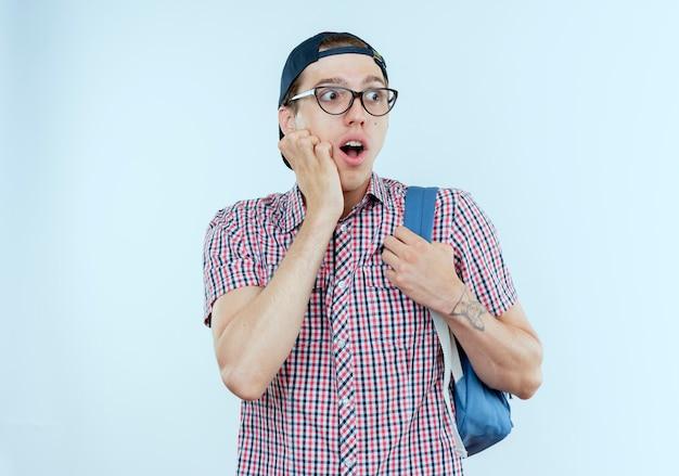 Patrząc na bok, zaskoczony młody uczeń chłopiec noszący torbę i okulary oraz czapkę kładącą rękę na policzku