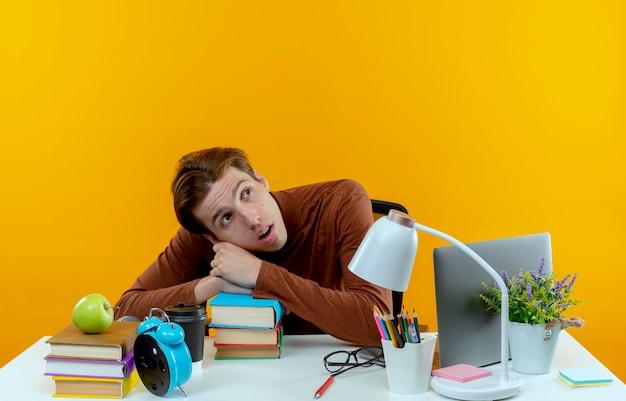 Patrząc na bok zaskoczony młody uczeń chłopiec siedzi przy biurku z narzędziami szkolnymi, kładąc głowę na książkach