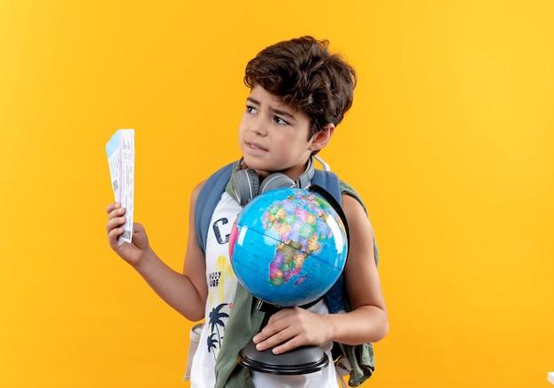 Patrząc na bok, zdezorientowany mały chłopiec w szkole, noszący torbę i słuchawki, trzymający bilety i kulę ziemską