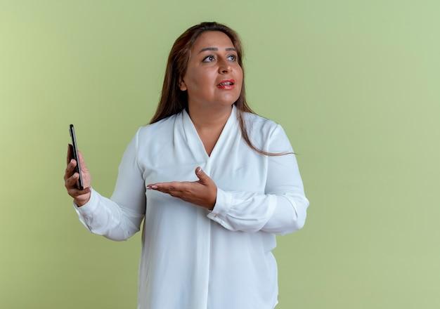Patrząc na bok, zdziwiona przypadkowa kaukaska kobieta w średnim wieku trzymająca rękę i wskazująca ręką na telefon