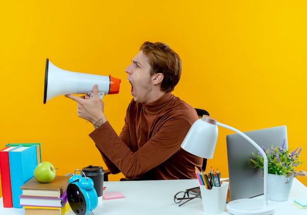 Patrząc na bok zły młody uczeń chłopiec siedzi przy biurku z narzędziami szkolnymi mówi na głośniku