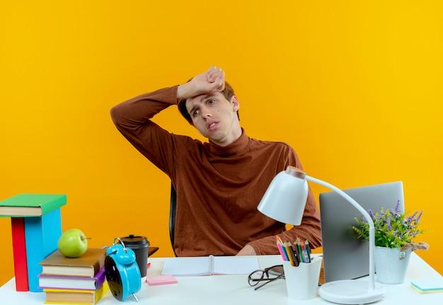 Patrząc na bok zmęczony młody uczeń chłopiec siedzi przy biurku z narzędziami szkolnymi, kładąc nadgarstek na czole