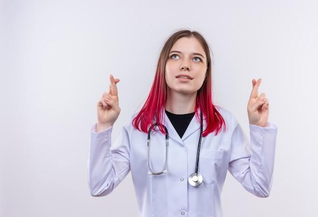 Patrząc na górę młoda dziewczyna lekarza noszenie szaty medycznej stetoskop skrzyżowane palce na na białym tle