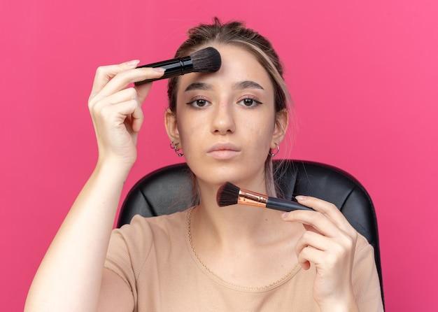 Patrząc na kamerę młoda piękna dziewczyna siedzi przy stole z narzędziami do makijażu, stosując rumieniec w proszku na różowej ścianie