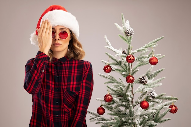 Patrząc na kamerę młoda piękna dziewczyna stojąca w pobliżu choinki w świątecznym kapeluszu z okularami zakrytymi oczami ręką na białym tle
