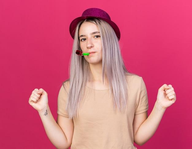 Patrząc na kamerę młoda piękna dziewczyna w kapeluszu imprezowym dmuchanie gwizdek pokazujący gest