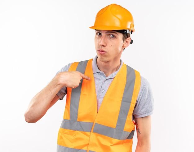 Patrząc na kamerę, młody budowniczy mężczyzna w mundurze wskazuje na siebie