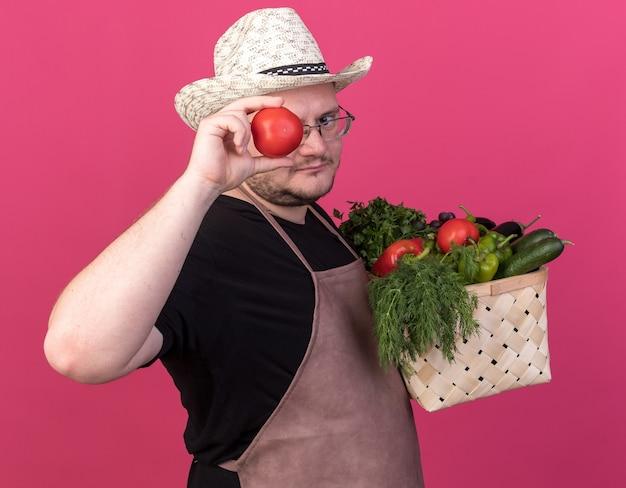 Patrząc na kamerę, młody mężczyzna ogrodnik w kapeluszu ogrodniczym, trzymający kosz warzyw, pokazujący gest spojrzenia z pomidorem odizolowanym na różowej ścianie