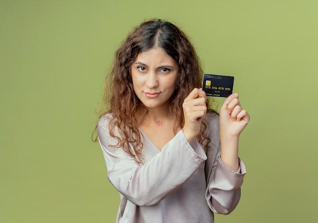 Patrząc na kamery młoda ładna kobieta pracownik biurowy trzyma kartę kredytową wokół twarzy