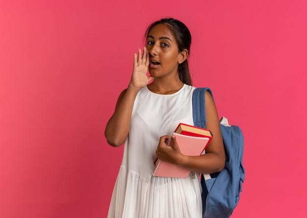 Patrząc na kamery młoda uczennica ubrana w torbę z powrotem trzymając książkę z notatnikiem i szepty
