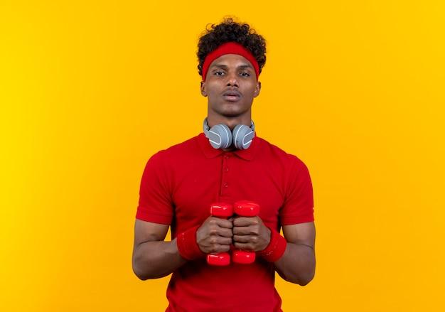 Patrząc na kamery młody sportowiec afro-amerykański noszenie pałąka i nadgarstka trzymając hantle