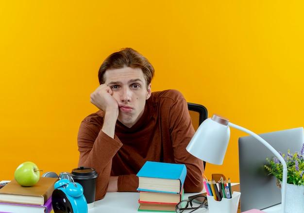 Patrząc na kamery młody uczeń chłopiec siedzi przy biurku z narzędzi szkolnych, kładąc głowę na nadgarstku