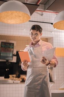 Patrząc na menu. przystojny, przyjemny, odnoszący sukcesy mężczyzna w okularach, patrząc na menu swojej kawiarni