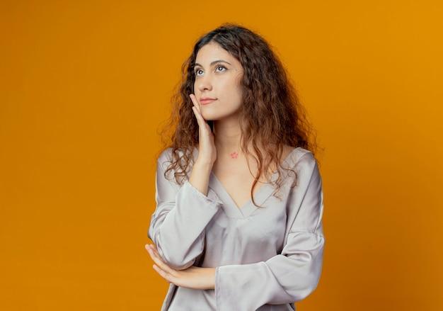 Patrząc na myślenie młoda ładna dziewczyna kładąc rękę na policzku na białym tle na żółtej ścianie