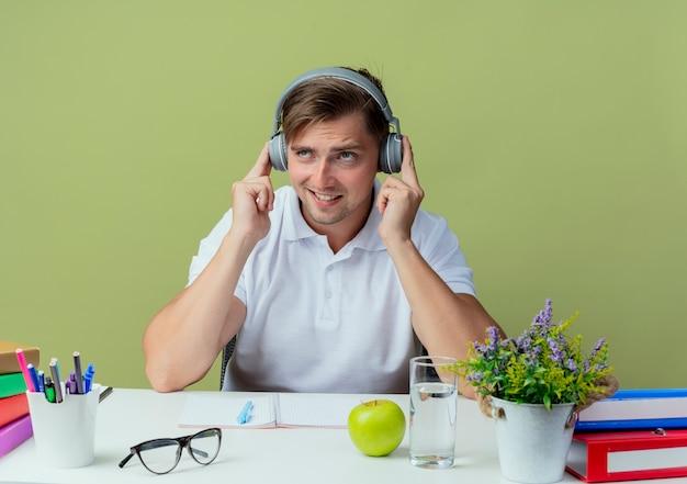 Patrząc na myślenie młody przystojny student płci męskiej siedzi przy biurku z narzędziami szkolnymi słuchaj na słuchawkach izolowanych na oliwkowej zieleni