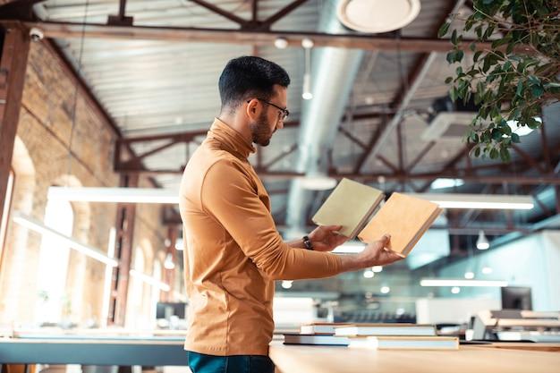 Patrząc na okładki. brodaty pisarz stojący w drukarni, patrzący na okładki książek, wybierający najlepszą