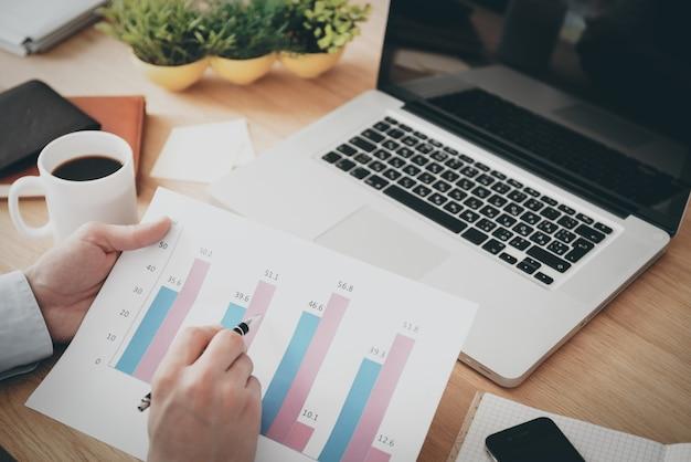 Patrząc na postęp firmy. widok z góry na mężczyznę trzymającego papier z diagramem podczas siedzenia w miejscu pracy