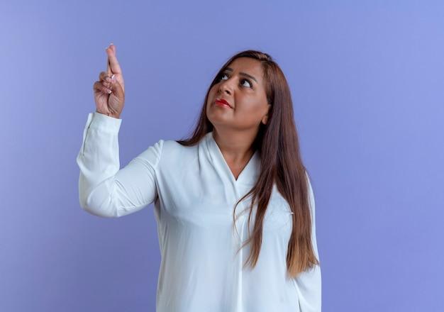 Patrząc na przypadkową kaukaska kobieta w średnim wieku, skrzyżowanymi palcami
