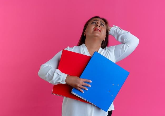 Patrząc na smutną, dorywczo kaukaską kobietę w średnim wieku, trzymając foldery i kładąc rękę na głowie