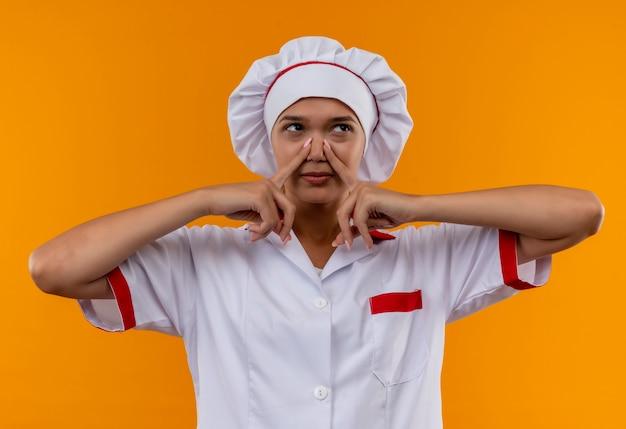Patrząc na stronę młoda kobieta kucharz ubrana w mundur szefa kuchni zamknięty nos na odizolowanych pomarańczowej ścianie