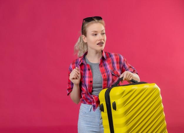 Patrząc na stronę młoda podróżniczka na sobie czerwoną koszulę i okulary na głowie trzymając walizkę na na białym tle różowej ścianie