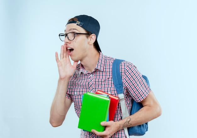 Patrząc na stronę młody uczeń chłopiec ubrany w tylną torbę i okulary i czapkę, trzymając książki i szepty