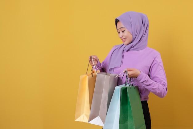 Patrząc na swoją torbę na zakupy, piękne azjatyckie zakupoholiczki trzymające torby na zakupy, wesołe i radosne