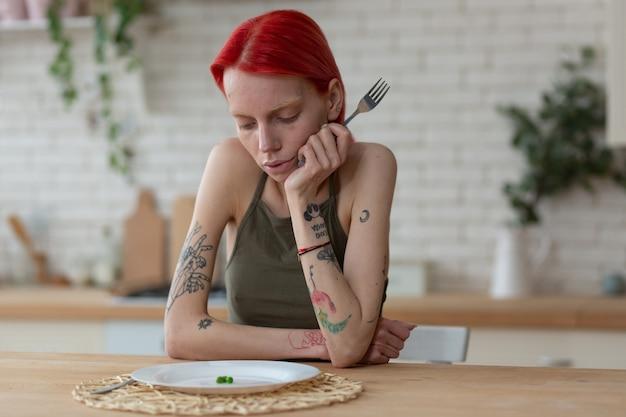 Patrząc na talerz. rudowłosa kobieta z bulimią trzyma widelec i patrzy na talerz z trzema zielonymi groszkami
