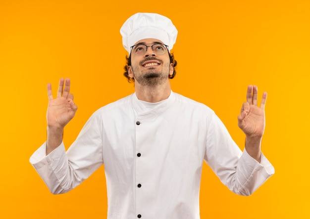 Patrząc na uśmiechnięty młody mężczyzna kucharz ubrany w mundur szefa kuchni i okulary pokazujące gest okey
