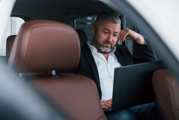 Patrząc na wyniki. praca z tyłu samochodu za pomocą laptopa w kolorze srebrnym. starszy biznesmen