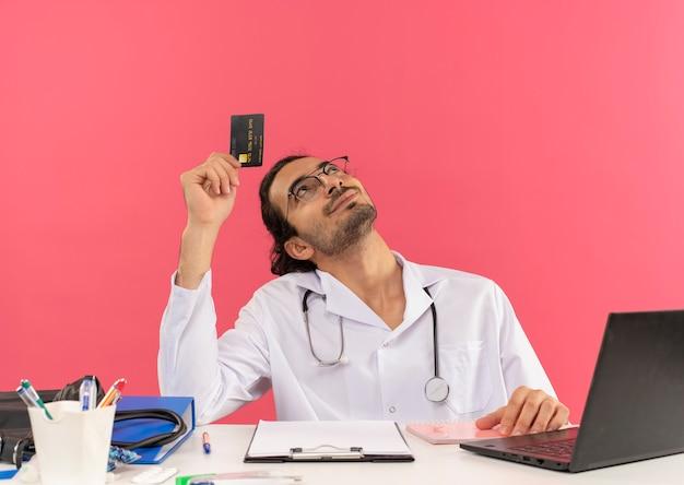 Patrząc na zadowolonego młodego lekarza mężczyznę w okularach medycznych, ubrany w szatę medyczną ze stetoskopem, siedzącego przy biurku