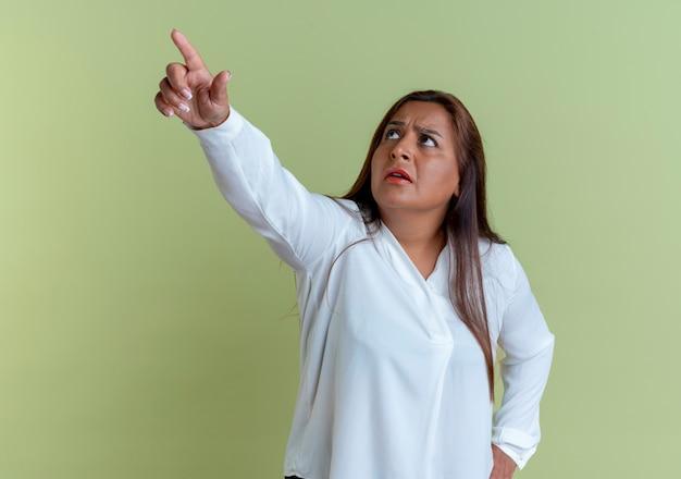 Patrząc na zdezorientowaną, przypadkową kaukaską kobietę w średnim wieku, wskazuje w górę i kładzie rękę na biodrze