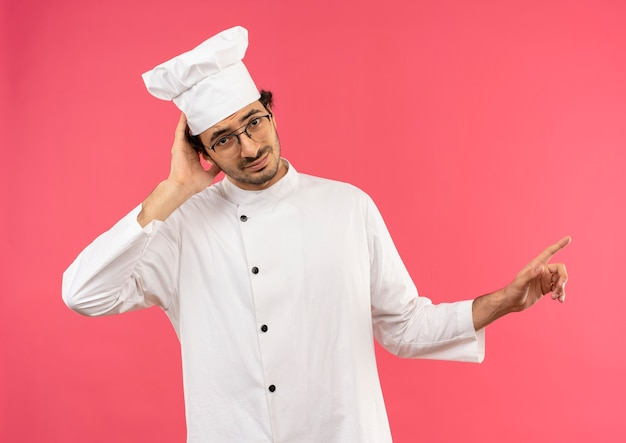 Patrząc na zdezorientowanego młodego kucharza w mundurze szefa kuchni i okularach, kładąc rękę na głowie i wskazując na bok