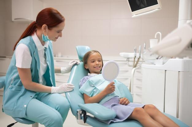 Patrząc na zęby. dziewczyna patrząca na zęby w lustrze podczas wizyty u dentysty rano