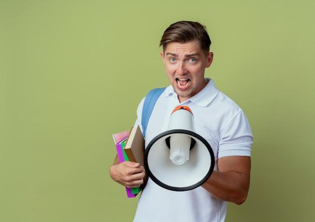 Patrząc na zły młody przystojny student płci męskiej noszący torbę z książkami i mówiący przez głośnik holding