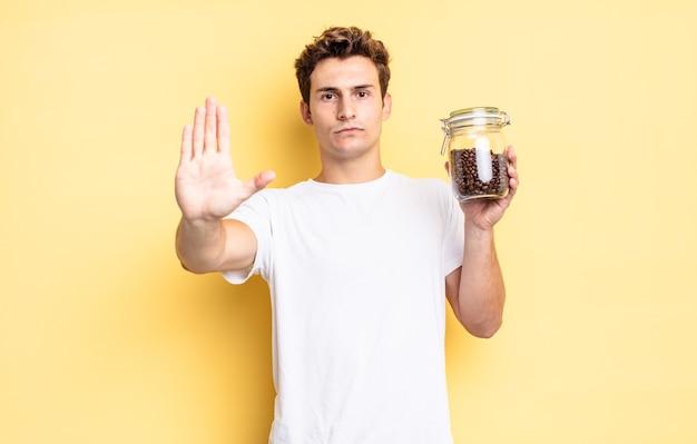 Patrząc poważnie, surowo, niezadowolony i zły pokazując otwartą dłoń, robiąc gest zatrzymania. koncepcja ziaren kawy