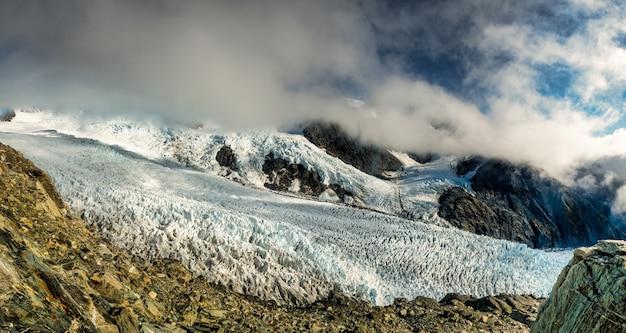 Patrząc przez krawędź na lodowiec franz josef poniżej i góry z zachmurzonym niebem