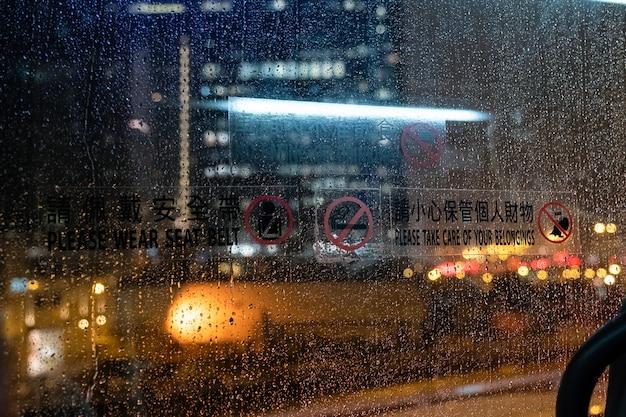 Patrząc przez okno w autobusie ze światłem na drodze w deszczowy dzień