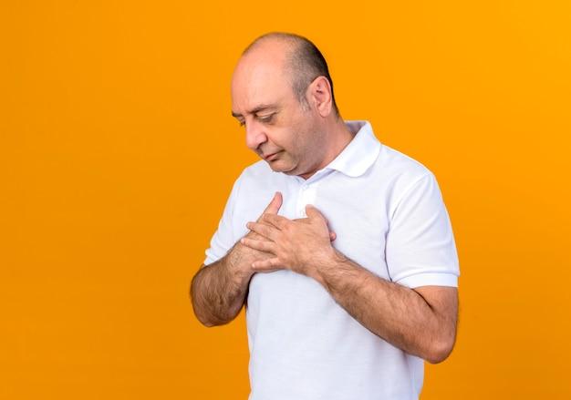 Patrząc w dół dorywczo dojrzały mężczyzna kładąc ręce na sercu