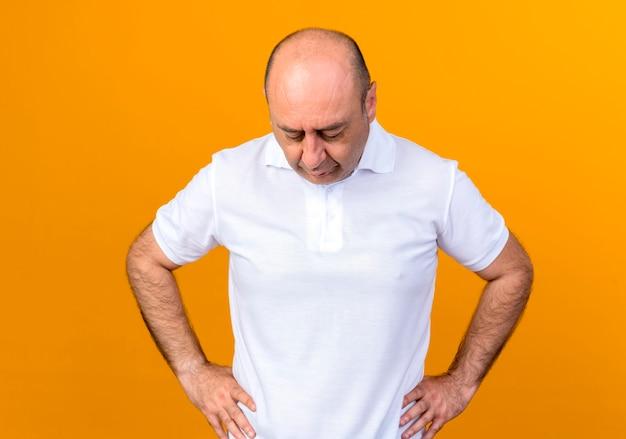 Patrząc w dół dorywczo dojrzały mężczyzna kładzie ręce na biodrze
