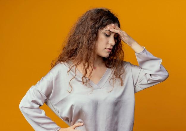 Patrząc w dół myślenia młoda ładna dziewczyna kładzie rękę na czole na białym tle na żółtej ścianie