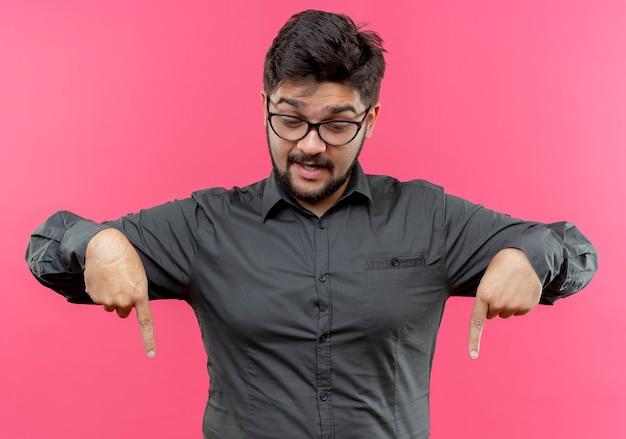 Patrząc w dół pod wrażeniem młody biznesmen w okularach wskazuje na dół na białym tle na różowej ścianie