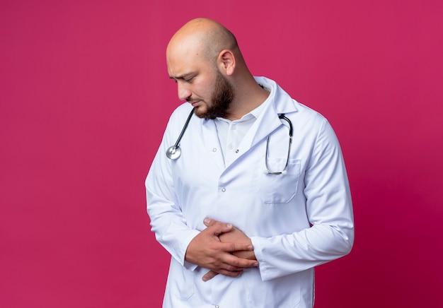 Patrząc w dół smutny młody lekarz mężczyzna ubrany w szlafrok i stetoskop złapał za brzuch