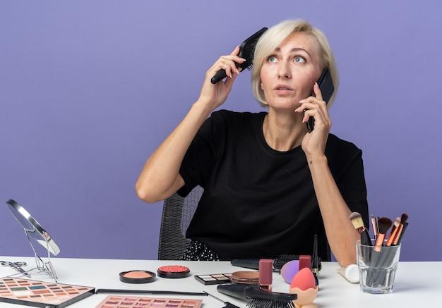 Patrząc w górę, młoda piękna dziewczyna siedzi przy stole z narzędziami do makijażu, rozmawia przez telefon, czesując włosy na niebieskiej ścianie