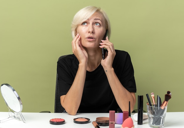 Patrząc w górę, młoda piękna dziewczyna siedzi przy stole z narzędziami do makijażu, rozmawia przez telefon, kładąc rękę na policzku odizolowaną na oliwkowozielonej ścianie