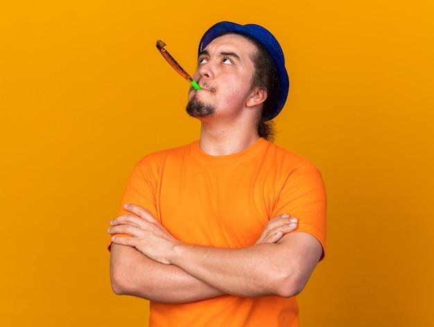 Patrząc w górę młody człowiek w kapeluszu imprezowym dmuchający gwizdek przechodzący przez ręce izolowane na pomarańczowej ścianie