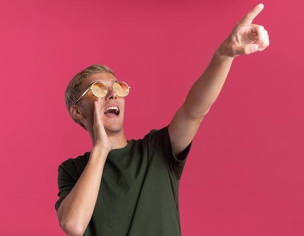 Patrząc w górę młody przystojny facet w zielonej koszuli i okularach, dzwoniąc do kogoś i wskazuje na bok na białym tle na różowej ścianie