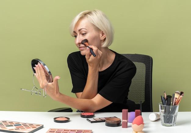 Patrząc w lustro młoda piękna dziewczyna siedzi przy stole z narzędziami do makijażu, nakładając pudrowy róż na białym tle na oliwkowozielonej ścianie