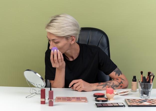 Patrząc w lustro młoda piękna dziewczyna siedzi przy stole z narzędziami do makijażu, nakładającymi krem tonujący z gąbką odizolowaną na oliwkowozielonej ścianie